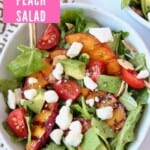 Salad in bowl topped with grilled peach slices and feta cheese