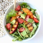 Overhead image of grilled peach salad in bowl
