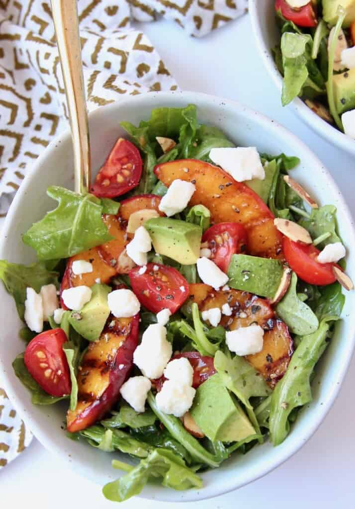 overhead image of salad in bowl with gold fork
