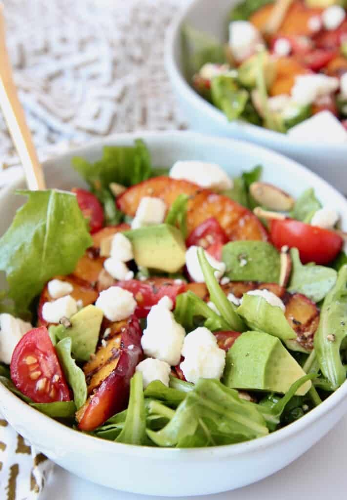 Salad in bowl, topped with diced avocado and tomatoes