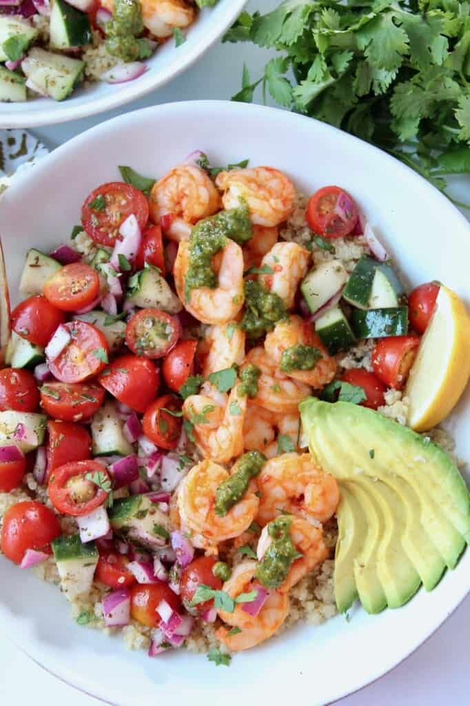 Overhead image of shrimp and tomato cucumber salad in bowl with sliced avocado