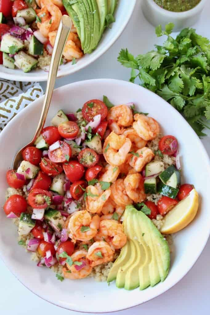 Overhead image of shrimp, avocado and diced tomatoes in bowl