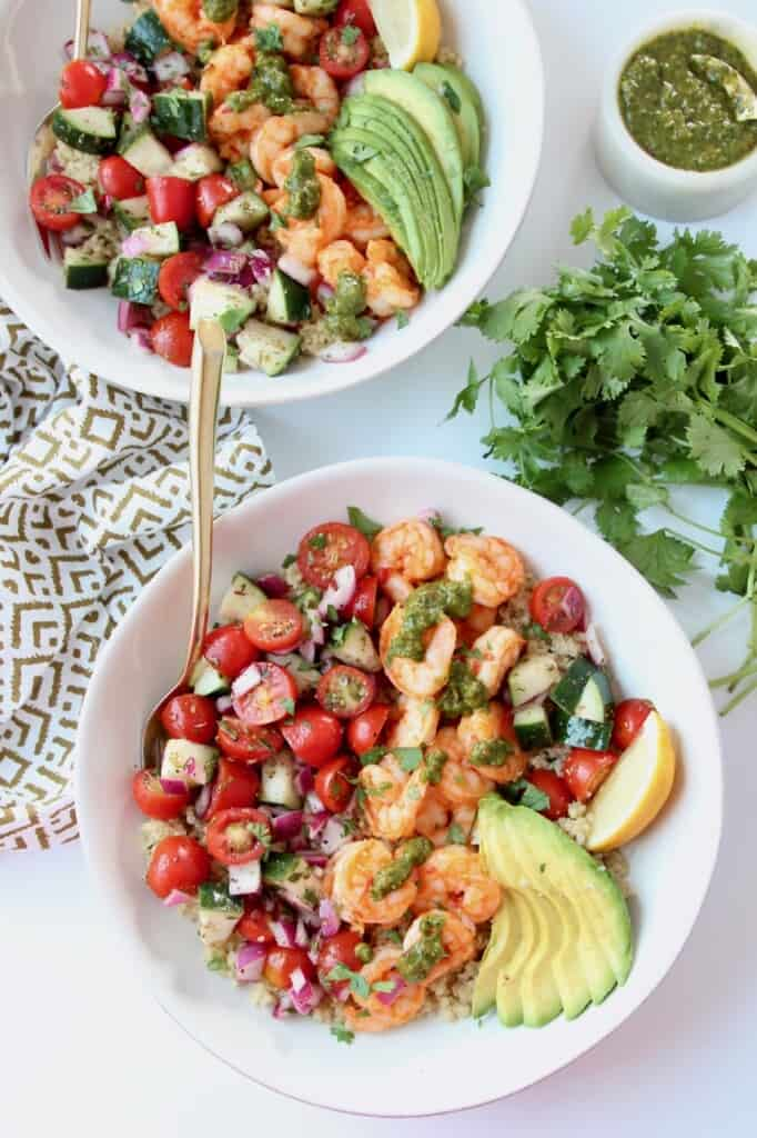 Overhead image of harissa shrimp in bowls with tomato cucumber salad