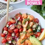 Overhead image of cooked shrimp in bowl with tomato cucumber salad