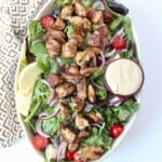 overhead image of grilled chicken on salad in bowl