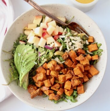 overhead image of kale sweet potato salad in bowl with sliced avocado and diced apples