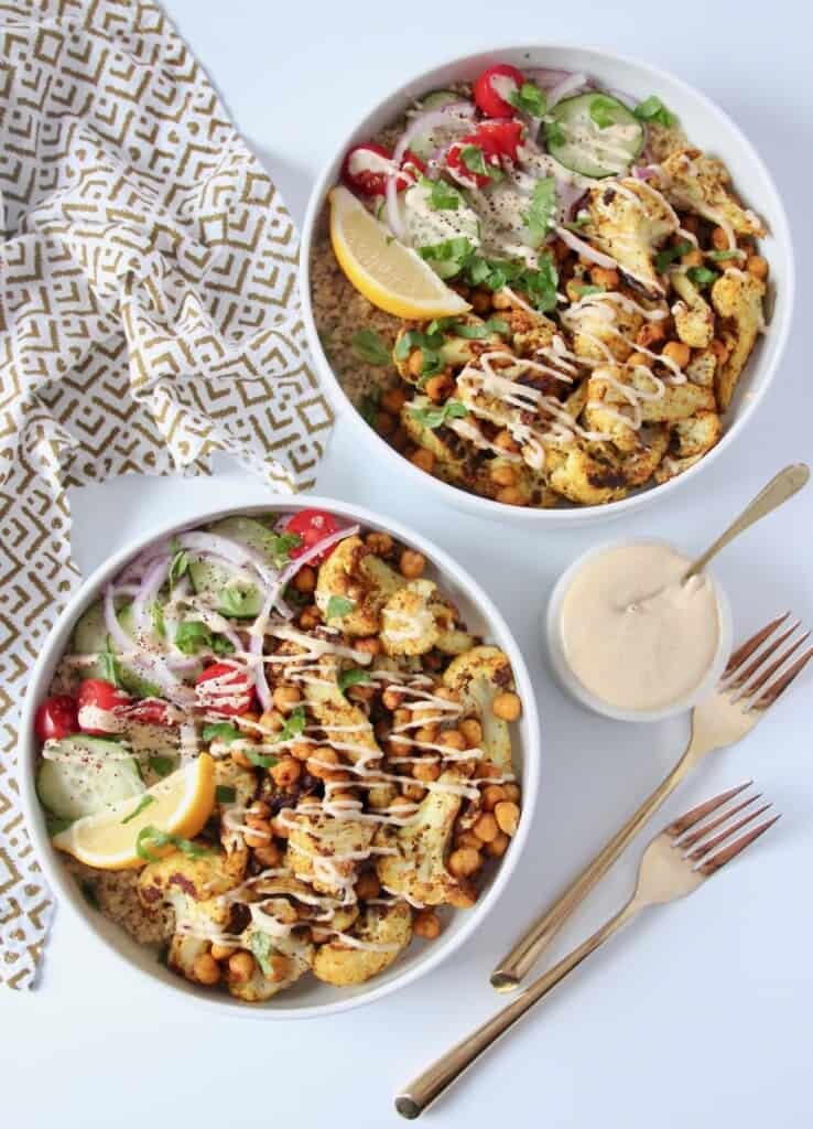 overhead image of two cauliflower shawarma bowls with tahini sauce in a small bowl on the side