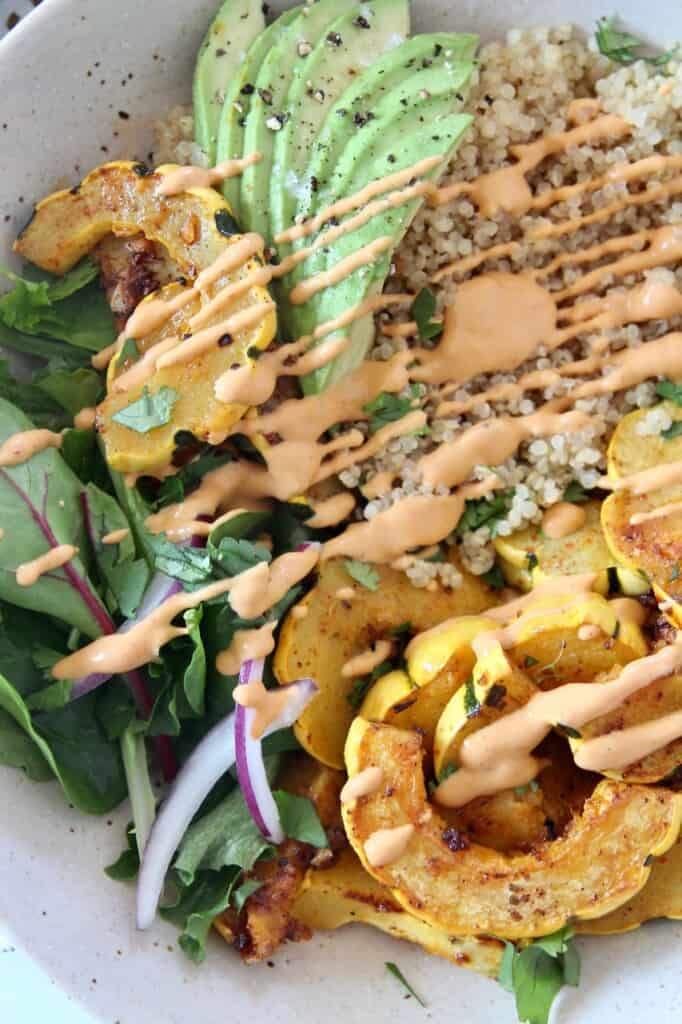 overhead image of roasted delicata squash in bowl with greens, avocado and quinoa