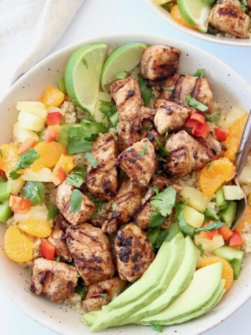 grilled pieces of chicken in bowl with diced fruit and peppers