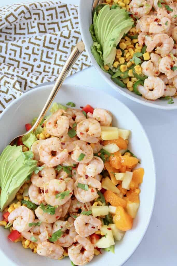 cooked shrimp salad in bowl with gold fork