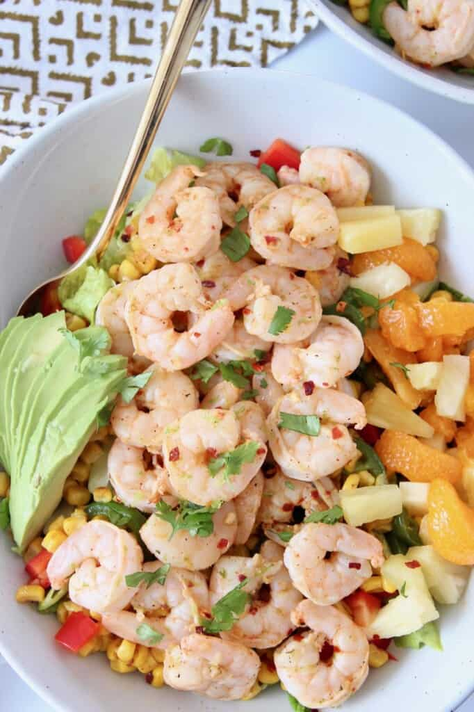 cooked shrimp on top of salad in bowl with gold fork