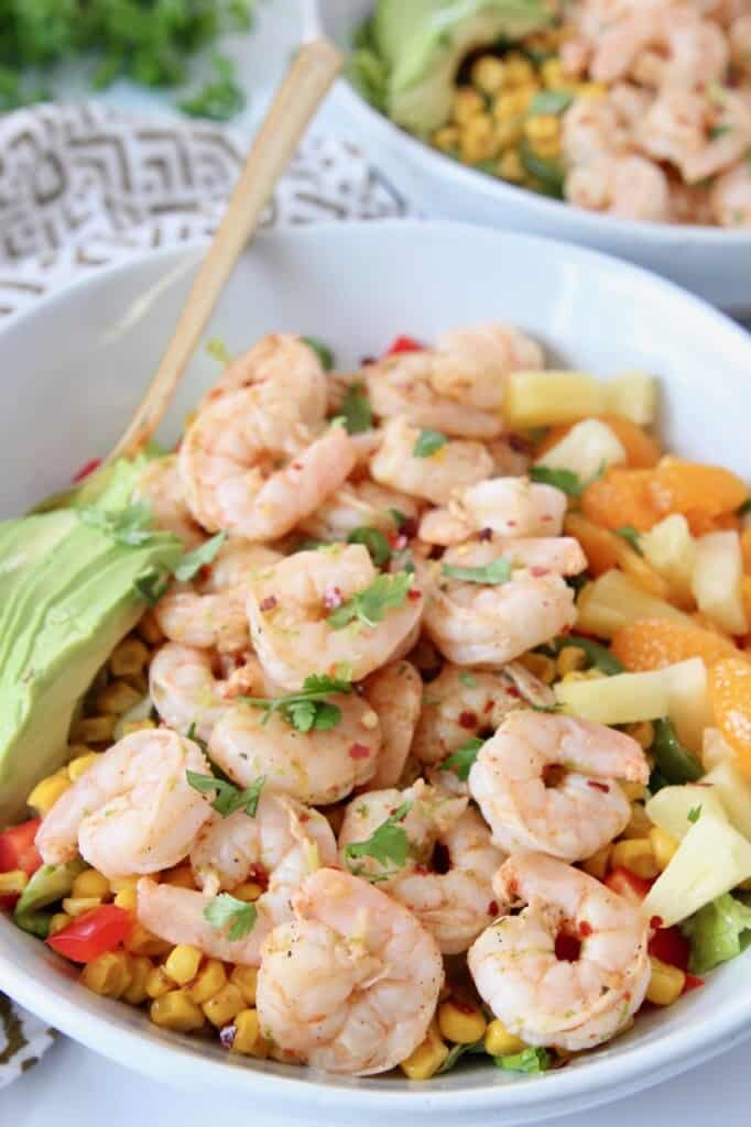 cooked shrimp in bowl with salad, sliced avocado and diced pineapple