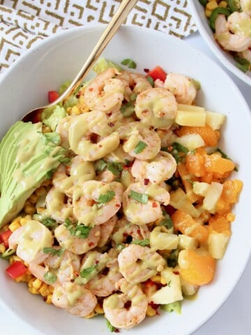 cooked shrimp in salad bowl topped with honey lime dressing