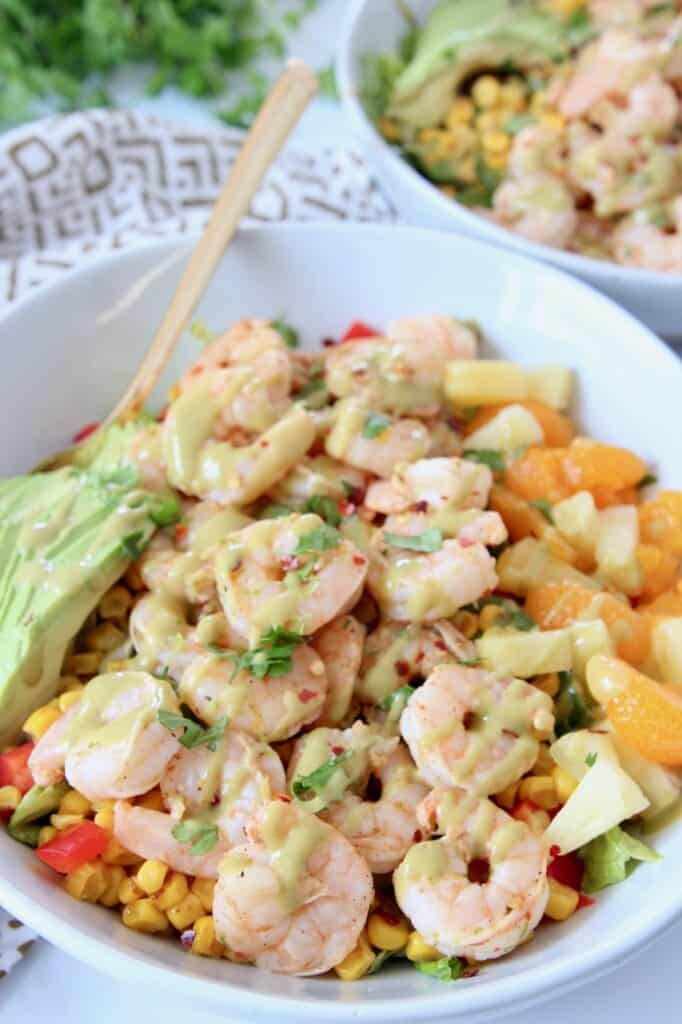 cooked shrimp is bowl with salad