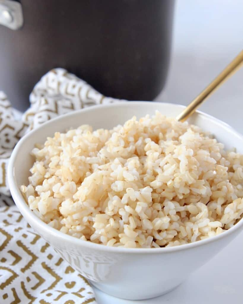 bowl of cooked brown rice sitting in front of a medium pot