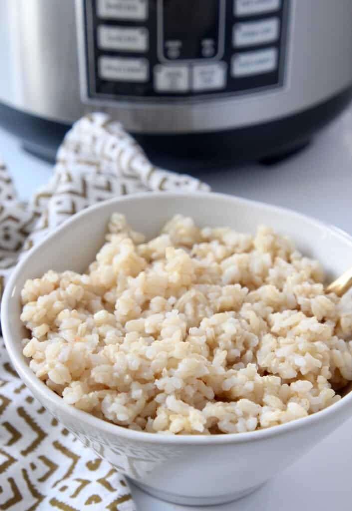 cooked brown rice in white bowl sitting in front of rice cooker