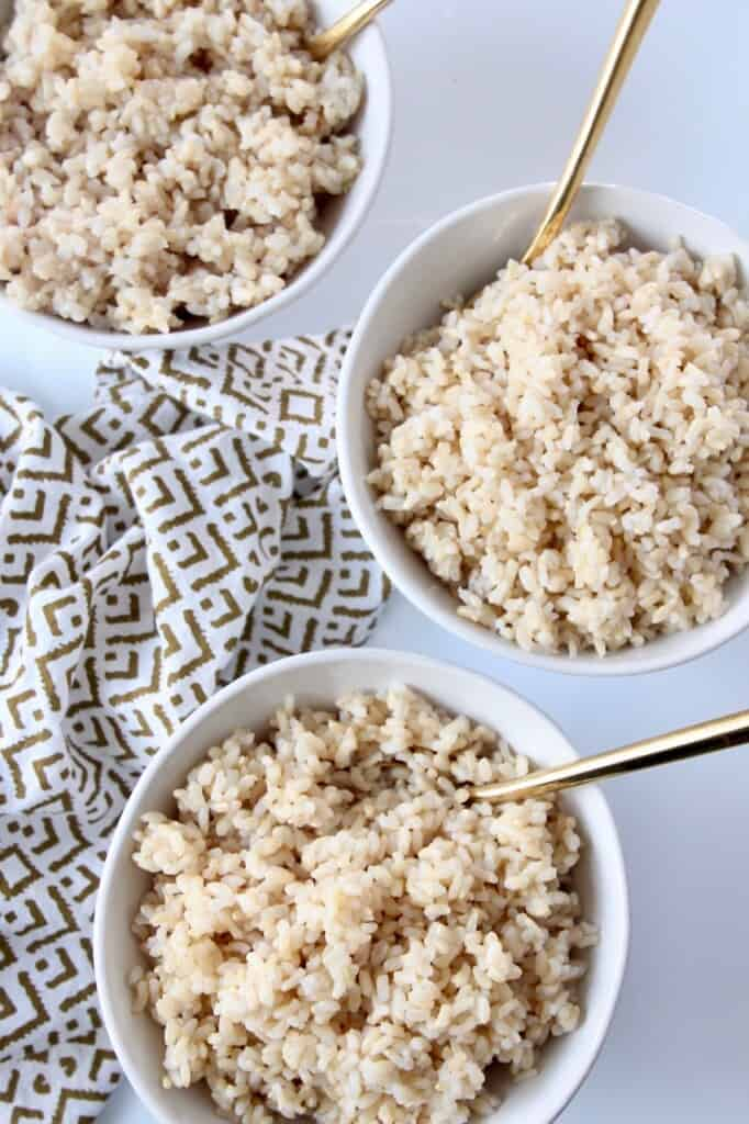 overhead image of 3 bowls of white rice with gold spoons