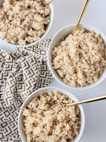 overhead image of 3 bowls of cooked brown rice with gold spoons