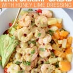 cooked shrimp on salad in bowl topped with honey lime salad dressing