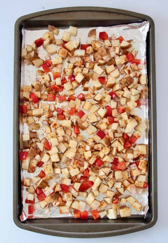 diced potatoes and bell peppers on foil lined baking sheet