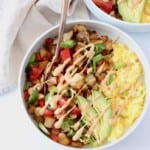 bowl filled with scrambled eggs, roasted potatoes and sliced avocado