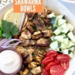 pieces of grilled chicken in bowl with diced cucumber and tomatoes