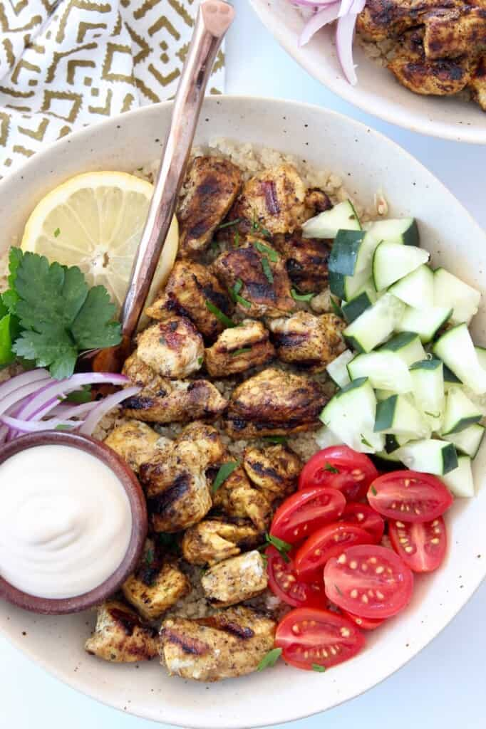 grilled chicken in bowl with fresh vegetables and garlic sauce