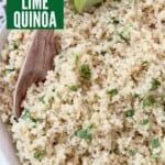 cooked quinoa tossed with cilantro in bowl with spoon and lime wedge