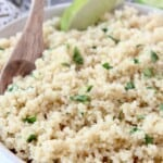 cooked quinoa in bowl with wooden spoon and lime wedge