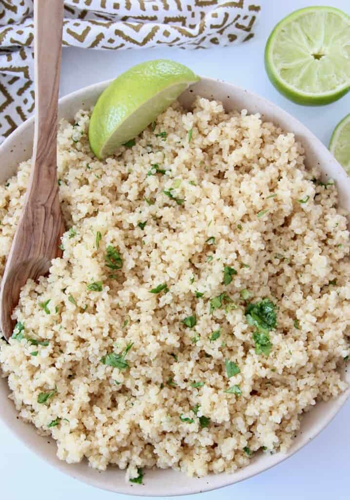 cooked quinoa mixed with fresh cilantro in bowl with lime wedge