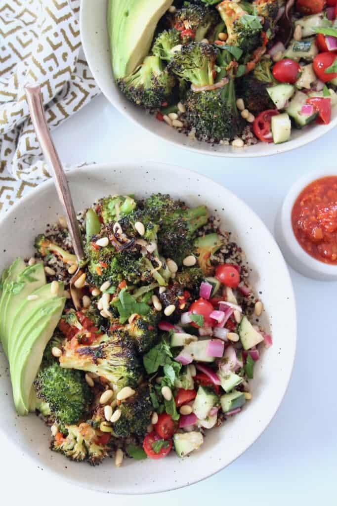 roasted broccoli in bowls with sliced avocado and diced tomato and cucumber salad