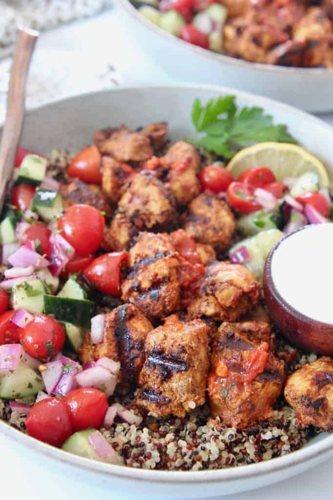 grilled chicken in bowl with quinoa and tomato cucumber salad