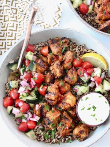 grilled cubes of chicken in bowl with diced tomato and cucumber and cooked quinoa