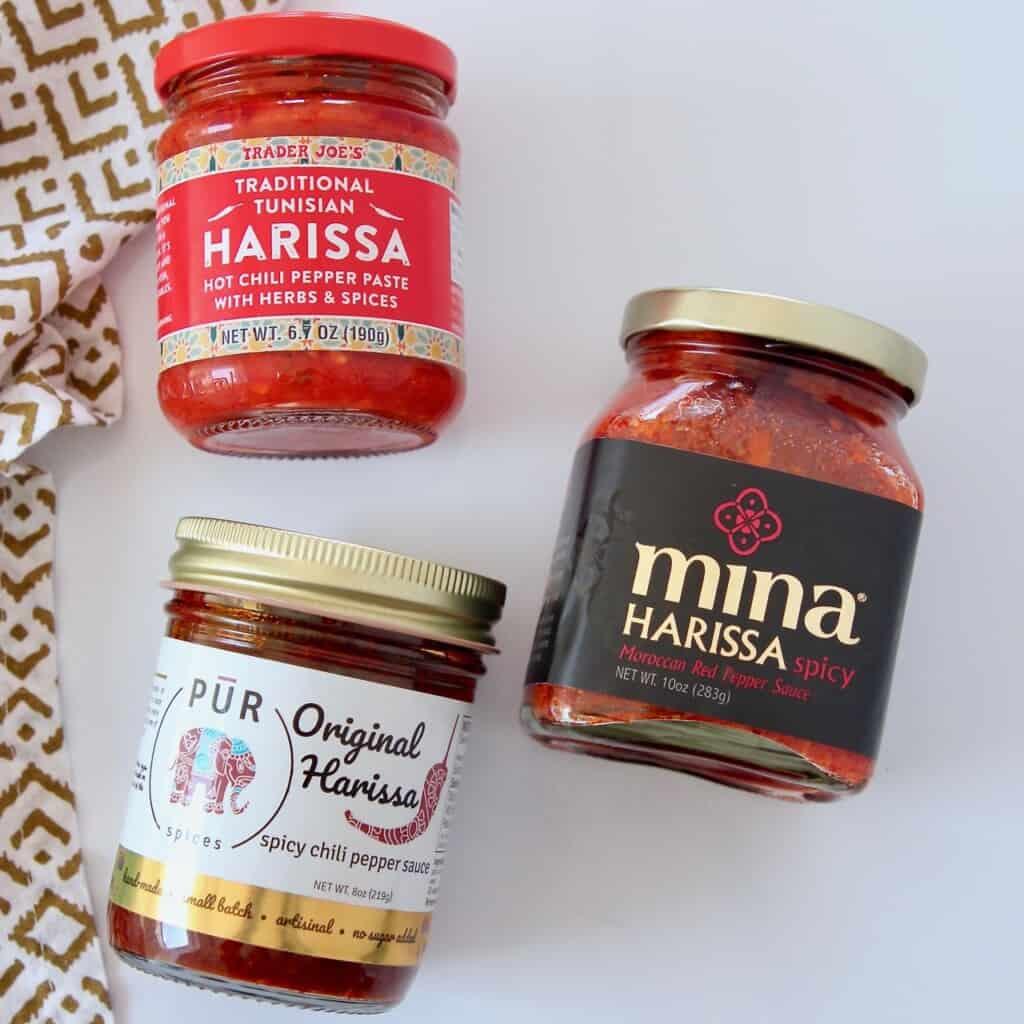three different branded jars of harissa