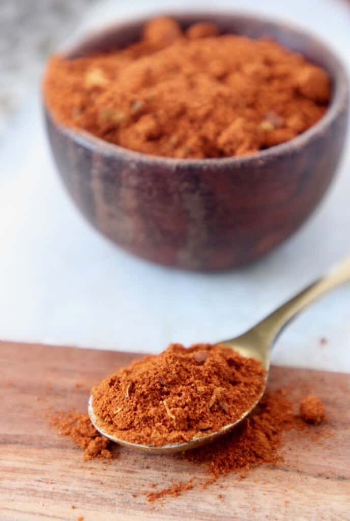 harissa seasoning in small wood bowl and in a small gold spoon