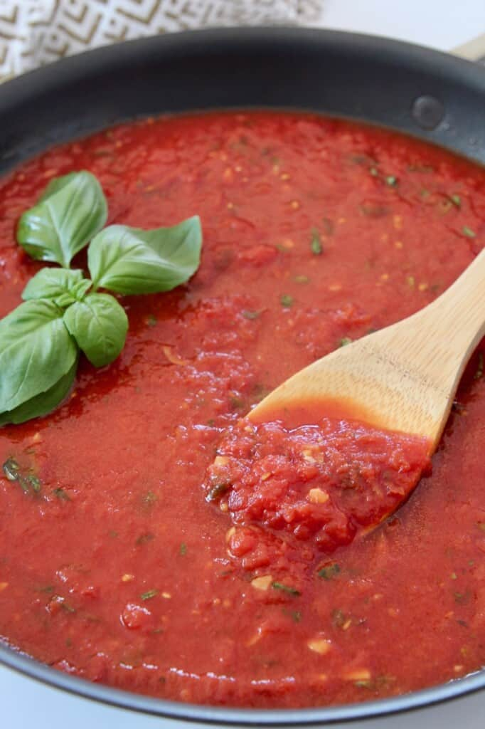 wooden spoon in marinara sauce in pan