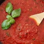 marinara sauce in skillet with wooden spoon and basil leaves