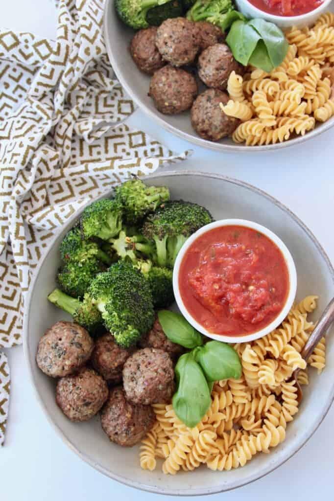 meatballs in bowl with marinara sauce, broccoli and rotini pasta