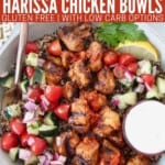 grilled pieces of harissa chicken in bowl with cucumber tomato salad and quinoa