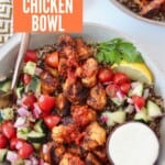grilled cubes of harissa chicken in bowl with tomato cucumber salad
