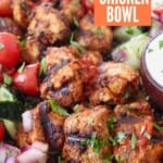 grilled pieces of chicken in bowl with quinoa and tomato cucumber salad