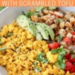 scrambled tofu in bowl with sliced avocado, tomatoes and roasted diced potatoes