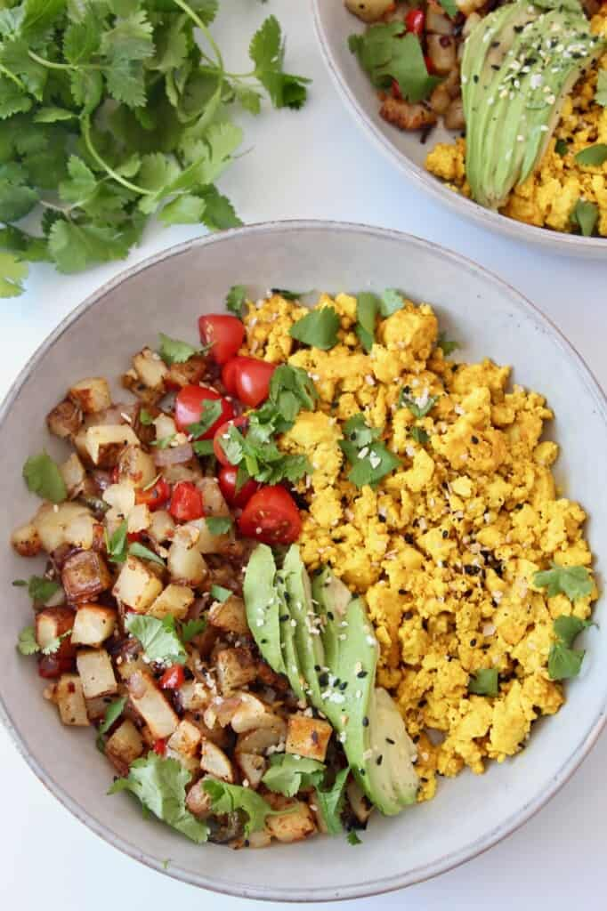 tofu scramble in bowl with diced roasted potatoes and sliced avocado