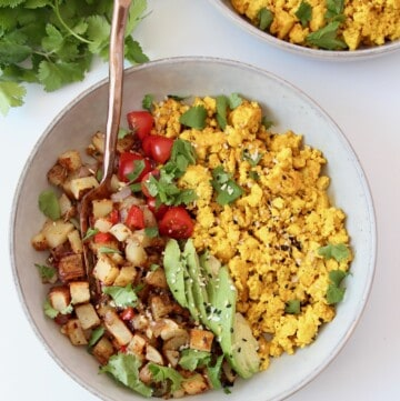 scrambled tofu in bowl with roasted potatoes, tomatoes and avocado