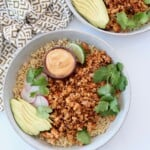 cooked crumbled tofu in bowl with quinoa and sliced avocado