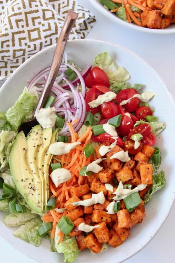 buffalo tofu bites on top of salad in bowl with avocado and tomato