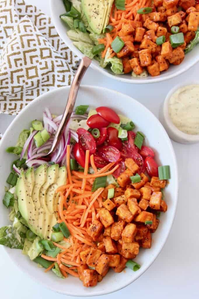 salad in bowl topped with cherry tomatoes, sliced avocado and buffalo tofu
