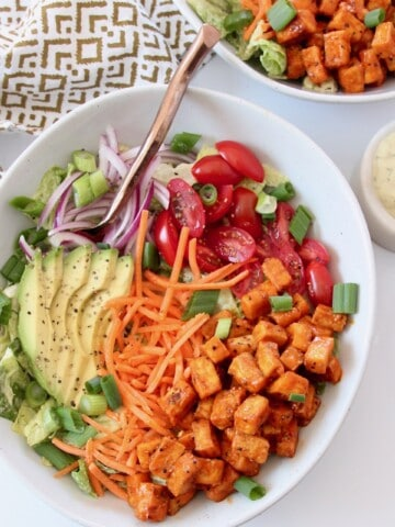 salad in bowl topped with buffalo tofu cubes, carrots, tomatoes and avocado
