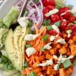 buffalo tofu cubes on top of salad in bowl with avocado, tomato, onion and avocado ranch dressing drizzle