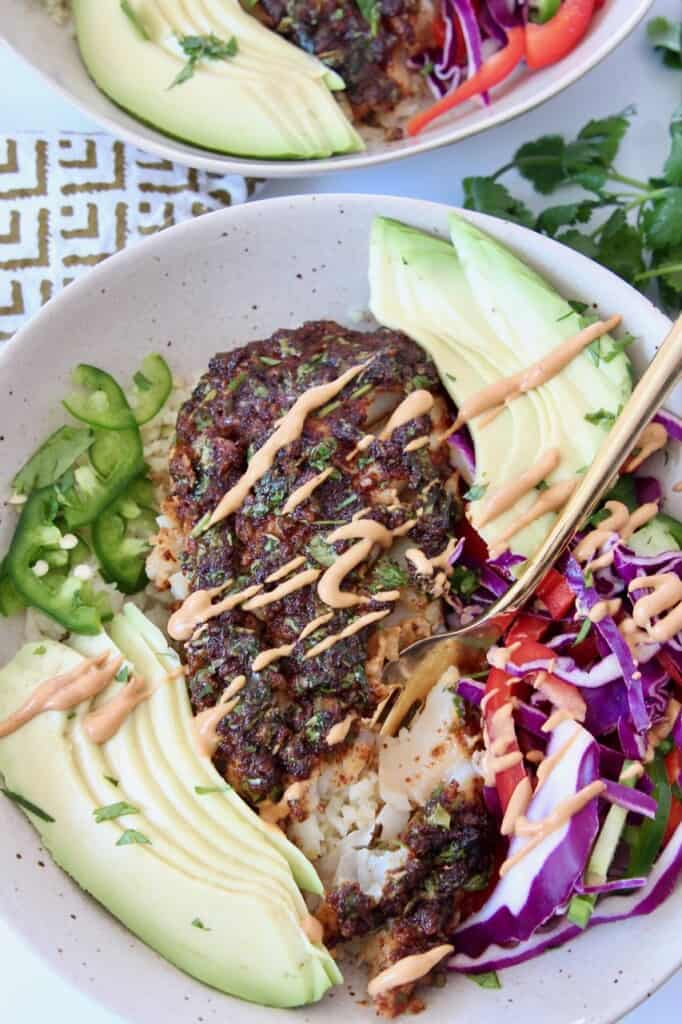 piece of baked cod in bowl with sliced avaocado and slaw
